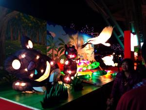 A nature scene with paper lanterns, including cranes, pandas, and turtles