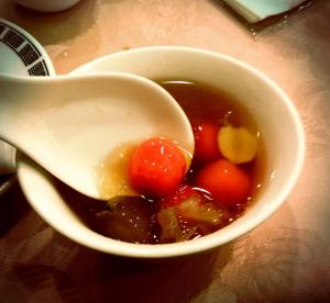 A traditional soup called tang yuan, which is made with a sweet broth, seaweed, and glutinous rice balls. It is supposed to bring luck and longevity to the couple