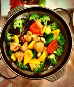 A traditional stir fry dish of broccoli, chicken, and peppers