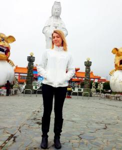 At Keelung Harbor in the north of Taiwan, standing with a statue of a Buddhist god